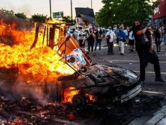 a protester stands next to a burning police car during the george floyd riots in minnesota