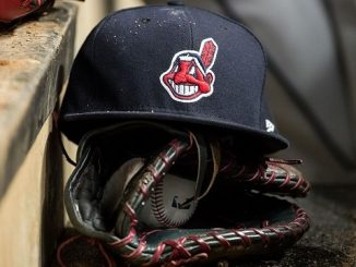 cleveland indians hat with chief wahoo logo laid atop a baseball mitt on the bench