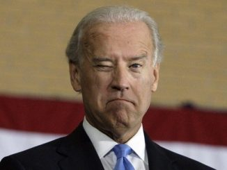 joe biden winking at camera in front of american flag