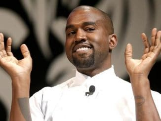 kanye west in a white shirt with his hands up