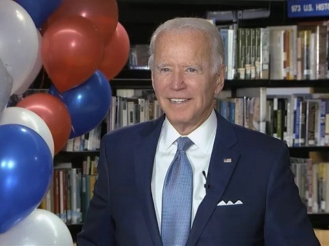 joe biden standing next to some balloons while accepting the 2020 democratic nomination in his basement