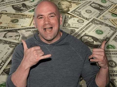 dana white smiling in front of a pile of dollar bills