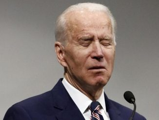 joe biden frowning with eyes closed at podium
