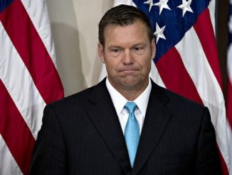 kris kobach frowning while standing in front of an american flag