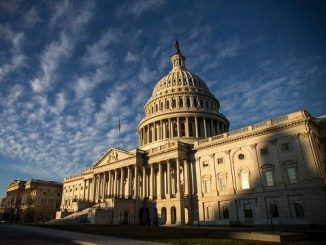 united states capitol building under a sunny sky with light clouds