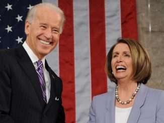 smiling joe biden standing next to smiling nancy pelosi in front of an american flag