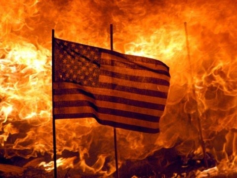 american flag flying in front of a burning fire