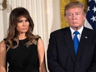 melania trump standing next to donald trump in front of an american flag