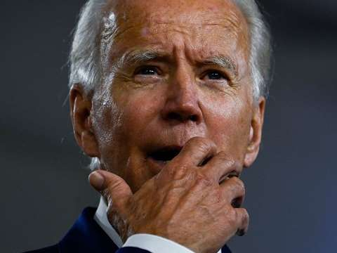 joe biden with his hand over his mouth