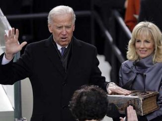 joe biden taking an oath with his hand on the bible